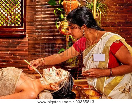 Indian woman does facial mask at ayurveda spa.