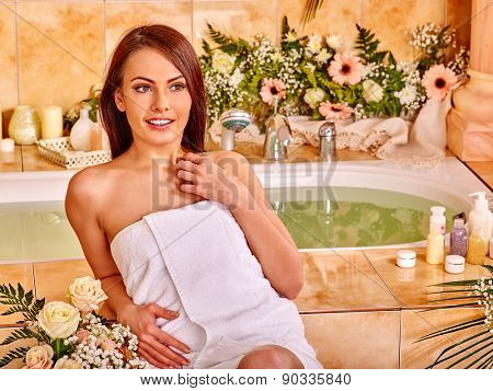 Woman relaxing at flower water spa. Girl sitting near bath.