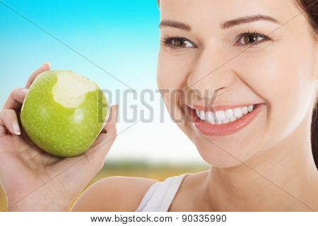 Happy woman eating an apple.