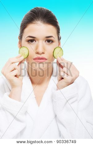 Woman in bathrobe with piece of cucumber.