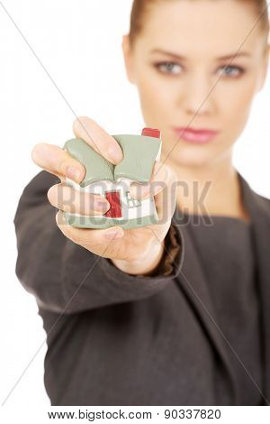 Aggresive businesswoman crushing small house.
