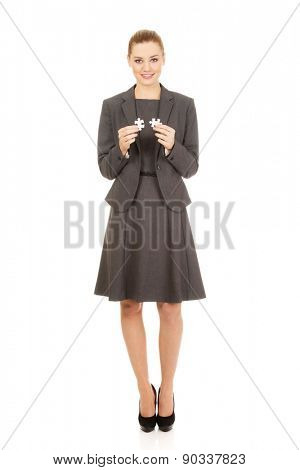 Happy businesswoman holding two puzzles.