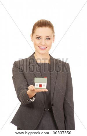 Businesswoman holding small model house.