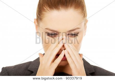 Young businesswoman suffering from sinus pain.