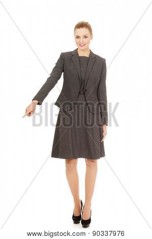 Young beautiful businesswoman pointing down.
