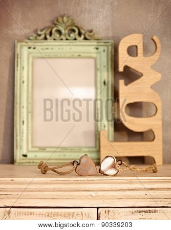 Romantic vintage home interior with worn frame, heart ornaments and love text.