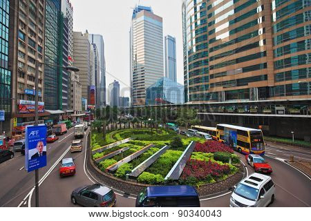 HONG KONG - DECEMBER 11, 2014: Hong Kong Special Administrative Region. Modern skyscrapers and narrow streets between them.  Fancy driving roundabout with colorful flower beds