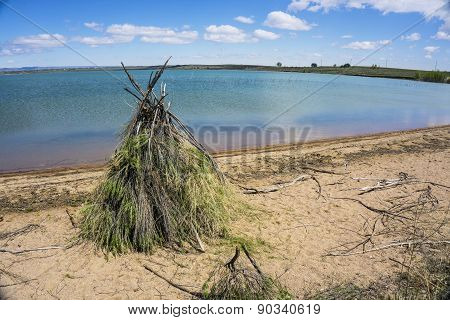 Colorful Grass Hut on a Sunny Lake Shore