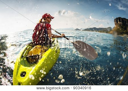 Young lady paddling the kayak in the sea with lots of splashes
