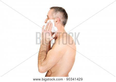 Side view of a man applying shaving foam.