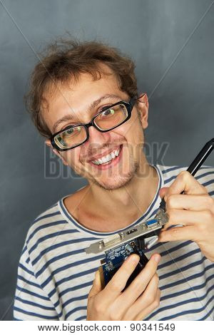 Young man use iron soldering electric parts