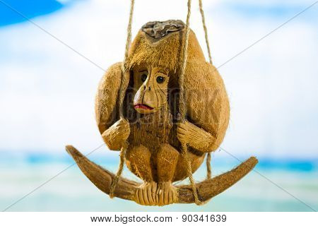 Coconut monkey on a swing at the beach.