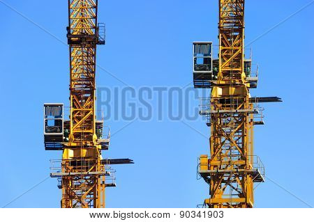 Two construction cranes