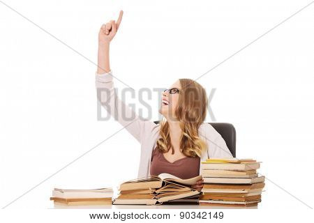 Happy teenage woman with stack of books pointing up