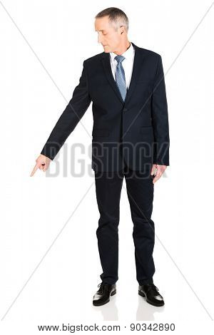 Mature businessman pointing down on the floor.