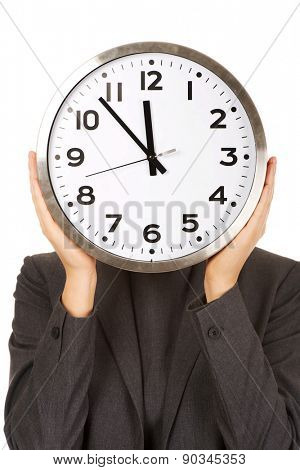 Business woman covering face with clock.