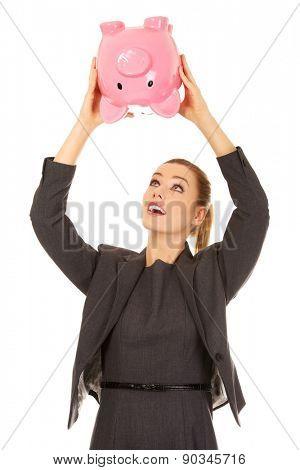 Happy business woman shaking a piggybank.