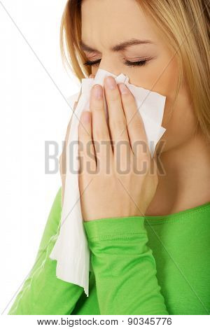 Ill woman sneezing to tissue.