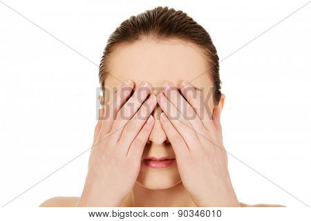 Caucasian woman covering her eyes.