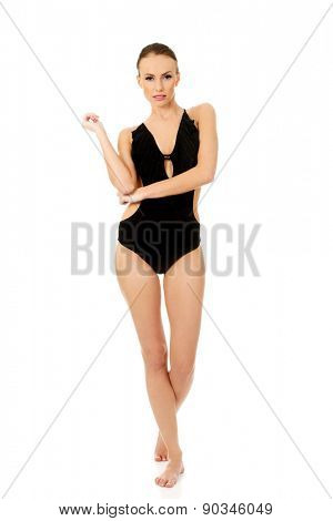 Happy young woman in black swimsuit.