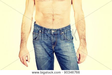Close up on shirtless men in jeans trousers.