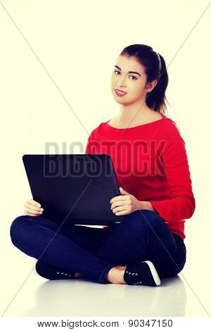 Front view woman sitting cross-legged with laptop.