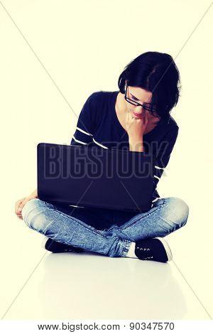 Pensive woman sitting cross-legged with laptop.