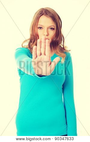 Young teenage woman making stop gesture