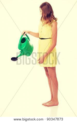 Teenage woman wearing skirt, holding watering can