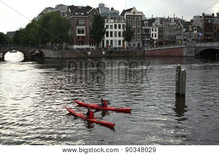 AMSTERDAM, NETHERLANDS - AUGUST 8, 2012: Two people on canoes training in the Amstel River near the Dutch National Opera in Amsterdam, Netherlands.