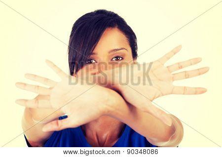 Young mulato woman making stop sign.
