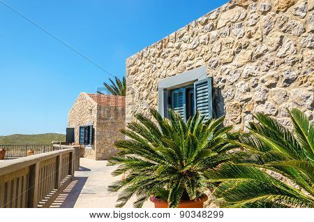 Typical wall of old Greek buildings and palm trees