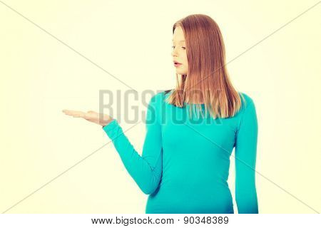 Teenage woman presenting something on palm