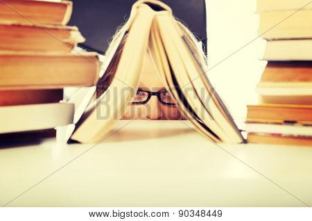 Happy teenage woman hiding behind a book