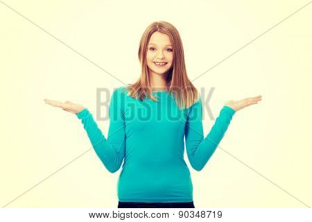 Confused teenage woman shrugging with palms up