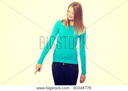 Happy teenage woman pointing down