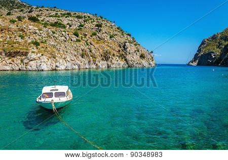 Small white motorboat anchored in sea bay, Greece