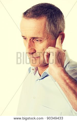 Mature man covering his ear.