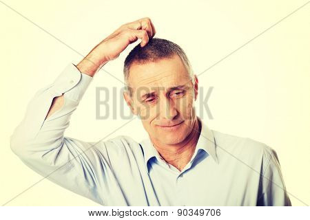 Mature confused man scratching his head.