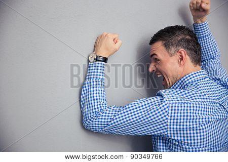Angry man shouting and hitting gray wall