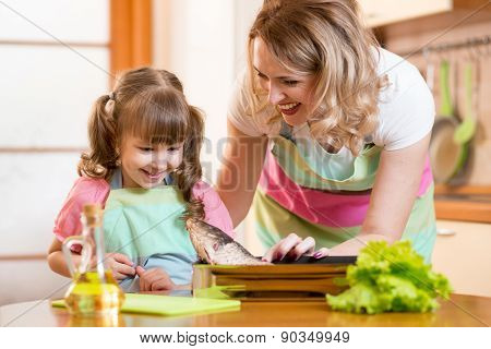 kid girl with mom cooking fish in the kitchen