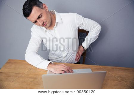 Businessman sitting at the table and having backache