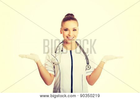 Female doctor presenting something in both hands.
