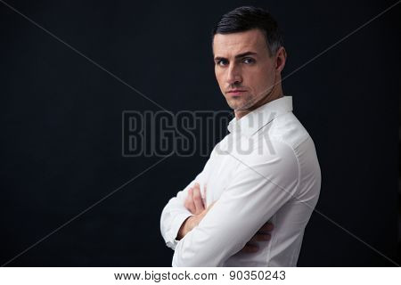 Portrait of a serious businessman with arms folded over black background and looking at camera