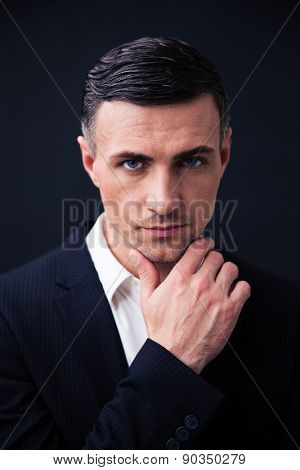 Handsome businessman in formal wear looking at camera over black background