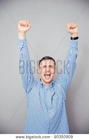 Man raised hands up over gray background. Making victory gesture. Looking at camera