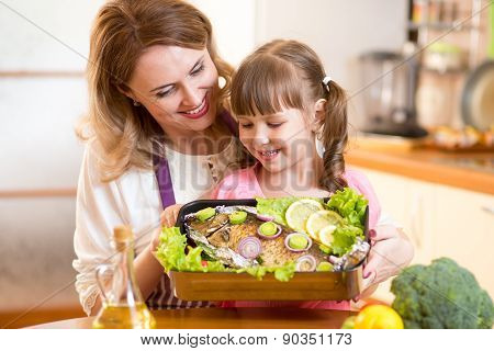 mother and child jolly look at prepared dish of fish