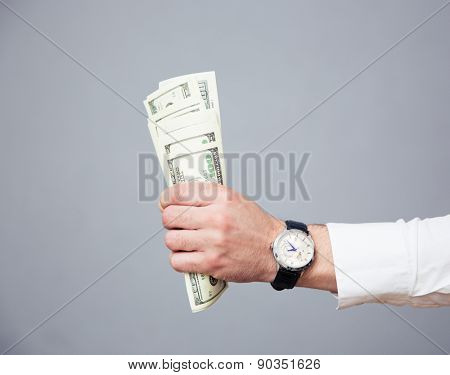 Closeup image of a businessman hand holding bills of US dollar over gray background