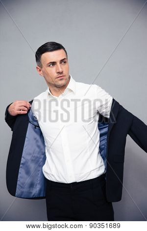 Handsome businessman dressing jacket over gray background and looking away