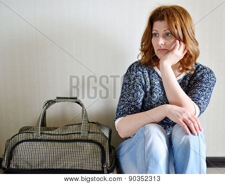 Sad Woman Sitting Near The Wall With Suitcase Because Divorce